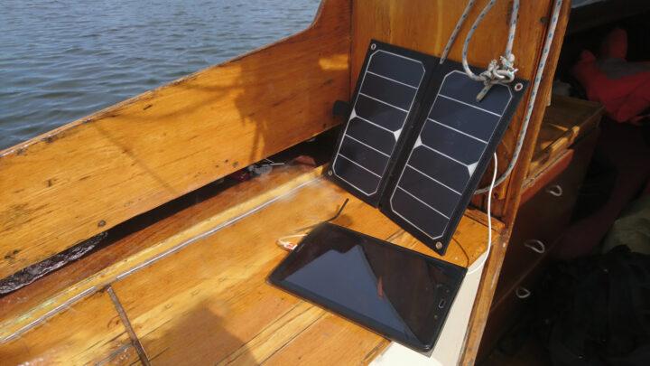 Tablet an Bord eines Jollenkreuzers mit Navigations-App und Solarpanel zur Stromversorgung.